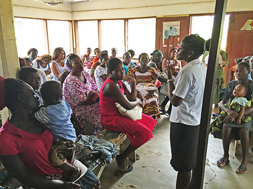 Sister Comfort talks to a group of women as part of her public health training.