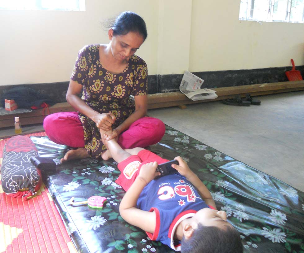 Sister Nirmola Maria Goretti Cruze, CSC, provides physical stimulation for a child with disabilities