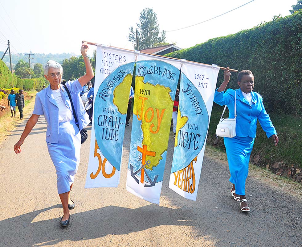 Sisters of the Holy Cross carry a banner to celebrate 50 years of service in Uganda